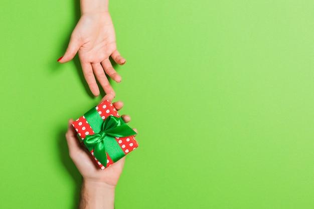 Draufsicht eines mannes und der frau, die eine geschenkbox halten. liebes- und beziehungskonzept. kopieren sie platz