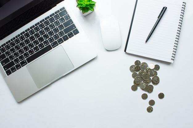 Draufsicht eines modernen weißen schreibtisches mit einer laptoptabelle, einem smartphone und anderen zusatzbuchhaltungskonzepten.