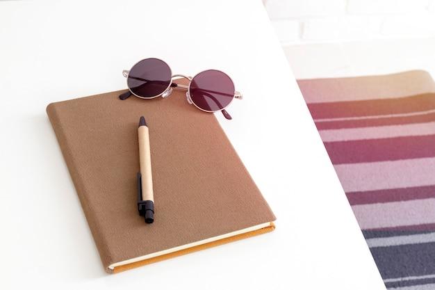 Draufsicht eines notizbuches, des stiftes und der sonnenbrille auf weißer tabelle.