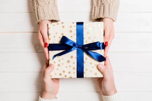 Draufsicht eines paares, das auf holztisch sich beglückwünscht. ein geschenk geben. festliches konzept. nahansicht