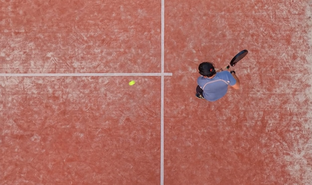 Draufsicht eines padelspielers, der während eines padelspiels oder eines trainings auf einem außenplatz den ball mit dem schläger schlagen wird