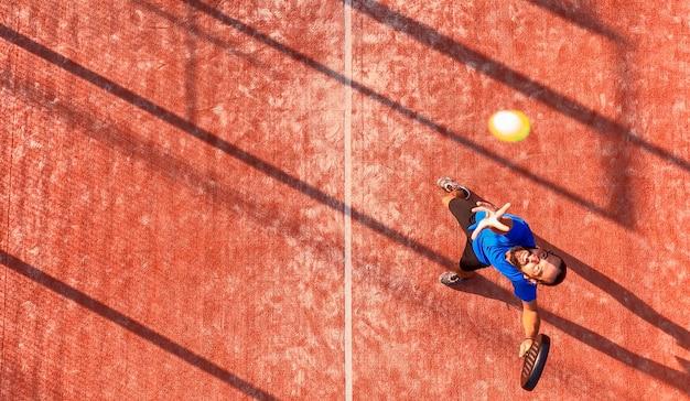 Draufsicht eines professionellen paddle-tennisspielers, der den ball während eines padel-matches schlagen wird. der ball ist sehr nah an der kamera.