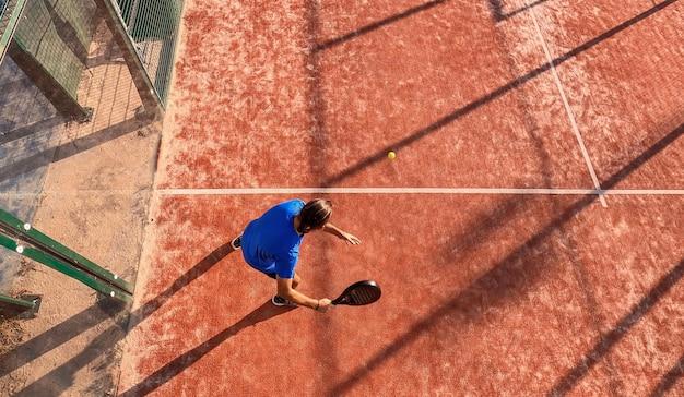Draufsicht eines professionellen paddle-tennisspielers, der ein padel-match auf einem außenplatz spielt.