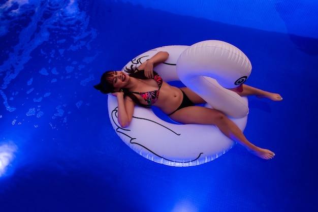 Draufsicht eines schönen glücklichen mädchens, das auf einem schwanschwimmer im pool schwimmt.
