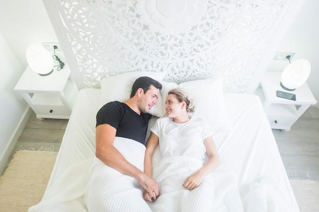 Draufsicht eines schönen jungen schönen paares, das zu hause in einem weißen bett schläft