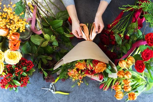 Draufsicht eines schönen straußes von roten, orange, burgunderfarbenen, gelben rosen, tulpen. sicht von oben. flache zusammensetzung