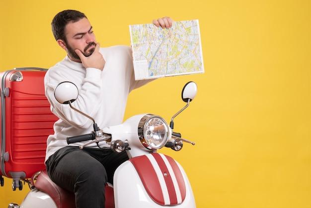 Draufsicht eines selbstbewussten jungen mannes, der auf einem motorrad mit koffer darauf sitzt und karte auf isoliertem gelbem hintergrund hält holding