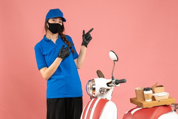 Draufsicht eines selbstbewussten kuriermädchens mit medizinischen maskenhandschuhen, das neben dem motorrad steht, mit kaffeekuchen darauf, der auf pastellfarbenem pfirsichhintergrund zeigt