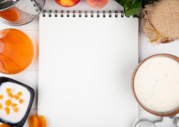 Draufsicht eines skizzenbuchs mit frischem pfirsichjoghurt-hüttenkäse und marmelade auf weiß