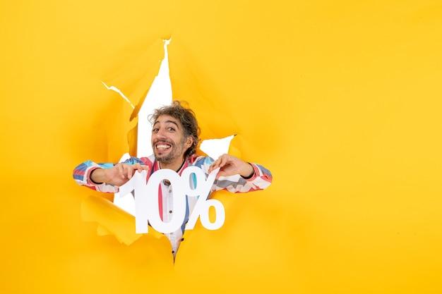 Draufsicht eines stolzen bärtigen mannes, der zehn prozent in einem zerrissenen loch in gelbem papier zeigt