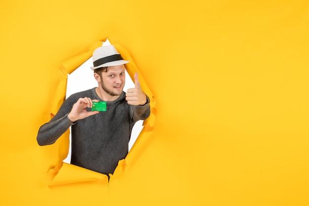 Draufsicht eines stolzen mannes, der eine bankkarte hält und eine ok geste in einer zerrissenen gelben wand macht
