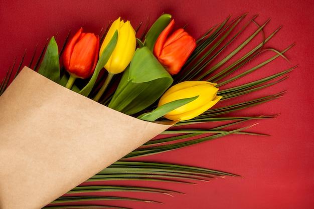 Draufsicht eines straußes der gelben und roten farbtulpen im bastelpapier mit palmblatt auf rotem tisch