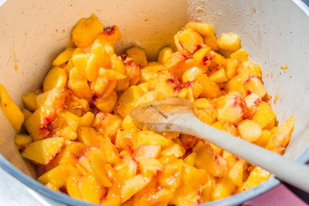Draufsicht eines topfes voll mit geschnittenen pfirsichen. hausgemachte pfirsichmarmelade kochen.