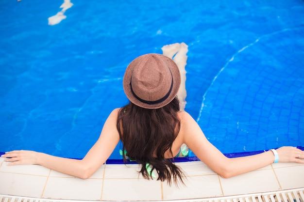 Draufsicht eines tragenden hutes der jungen frau im pool