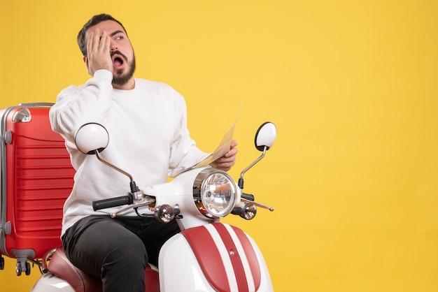Draufsicht eines übermüdeten jungen mannes, der auf einem motorrad mit koffer darauf sitzt und karte auf isoliertem gelbem hintergrund hält