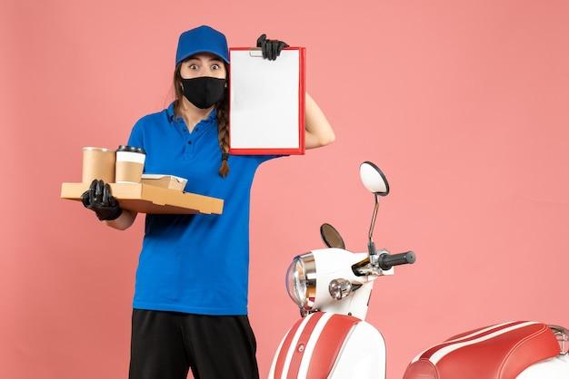 Draufsicht eines überraschten kuriermädchens mit medizinischen maskenhandschuhen, das neben dem motorrad steht