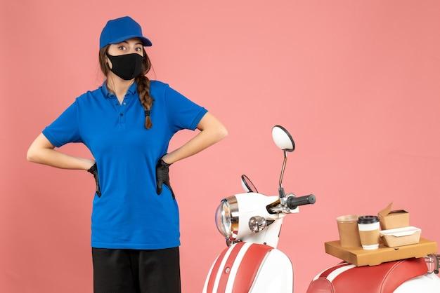 Draufsicht eines verwirrten kuriermädchens in medizinischer maske, das neben dem motorrad mit kaffeekuchen auf pastellfarbenem hintergrund steht