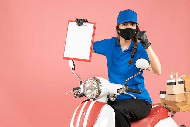 Draufsicht eines verwirrten kuriermädchens mit medizinischer maske und handschuhen, das auf einem roller sitzt und ein leeres papierblatt hält, das bestellungen auf pastellfarbenem pfirsichhintergrund liefert