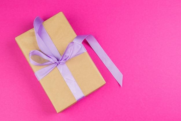 Draufsicht eines verzierten geschenkes mit einem bogen auf rosa hintergrund