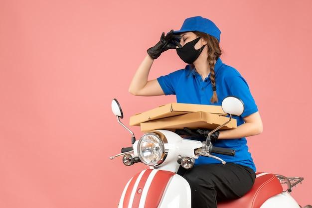 Draufsicht eines weiblichen kuriers mit medizinischer maske und handschuhen, der auf einem roller sitzt und bestellungen liefert, die eine schlechte geruchsgeste auf pastellfarbenem pfirsichhintergrund machen
