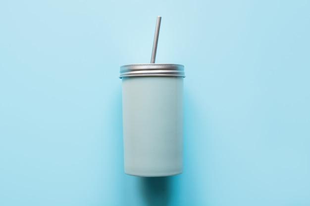 Draufsicht eines wiederverwendbaren glases mit einem metalldeckel und einem strohhalm für sommergetränke.