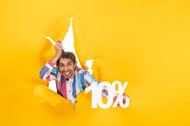 Draufsicht eines wütenden jungen mannes, der zehn prozent in einem zerrissenen loch in gelbem papier zeigt showing