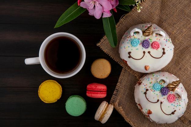 Draufsicht einhörner mit süßen donuts mit einer tasse tee und farbigen makronen auf einem holztisch