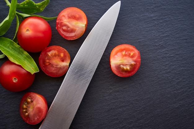 Draufsicht einiger kirschtomaten mit einem messer auf einem dunklen tisch. konzept der vegetarischen und gesunden ernährung.