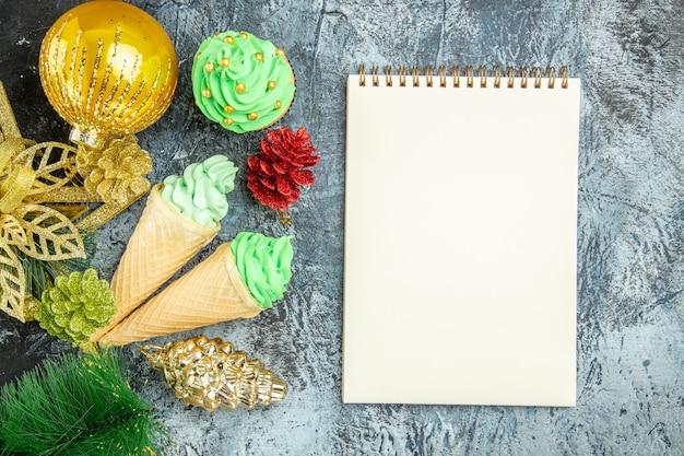 Draufsicht eiscreme weihnachtsbaum cupcake weihnachtsschmuck notizbuch auf grauem hintergrund