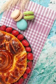 Draufsicht erdbeerkuchen mit französischen macarons auf blauem schreibtisch