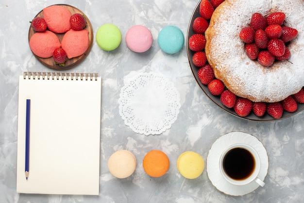 Draufsicht erdbeerkuchen mit frischen erdbeeren und tee auf weiß