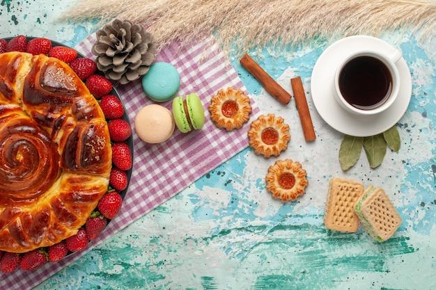Draufsicht erdbeerkuchen mit keksen french macarons und tasse tee auf blauer oberfläche