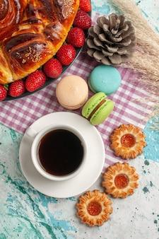 Draufsicht erdbeerkuchen mit keksen macarons und tasse tee auf blauer oberfläche