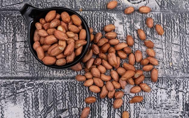 Draufsicht erdende erdnüsse in der schüssel auf holzgrau