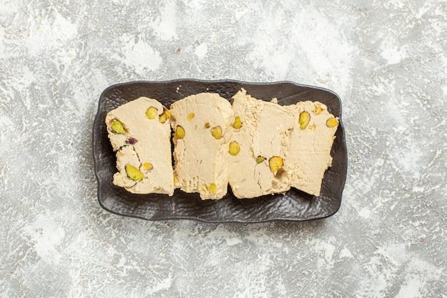 Draufsicht erdnuss-nougat-scheiben innerhalb platte auf weißem hintergrund