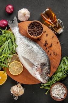 Draufsicht estragon frischer roher fisch schwarzer pfeffer schüssel auf rundem holzbrett ölflasche knoblauch rote zwiebel auf schwarz
