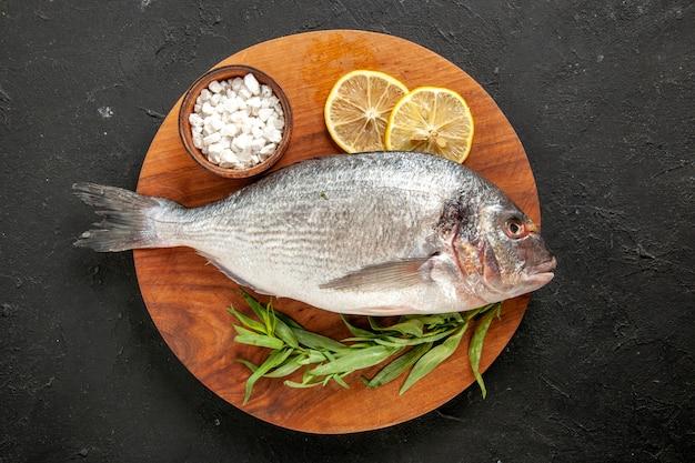 Draufsicht estragon roher seefisch meersalz in schüssel zitronenscheiben auf rundem holzbrett auf schwarz
