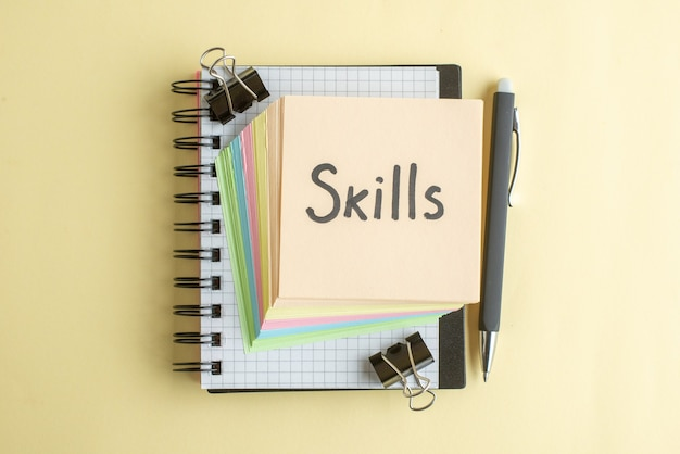 Draufsicht fähigkeiten geschriebene notiz zusammen mit bunten kleinen papiernotizen auf hellem hintergrund schule farbe notizblock job büroarbeit heft
