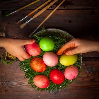 Draufsicht farbige eier mit samen und menschlicher hand in der weißen platte