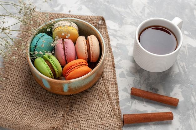 Draufsicht farbige französische macarons köstliche kleine kuchen mit tasse tee auf weißer oberfläche