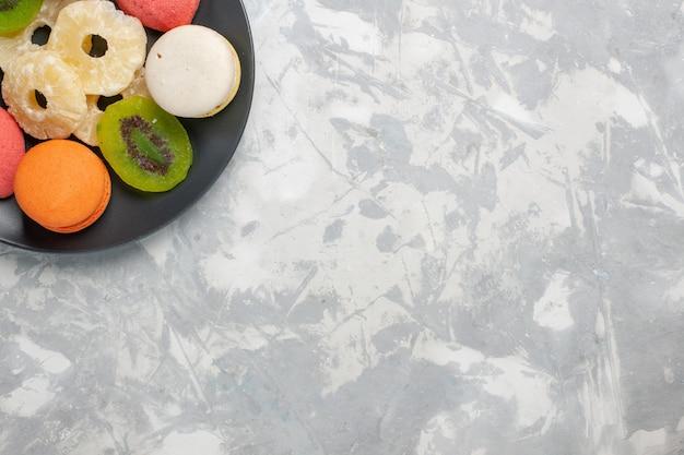 Draufsicht farbige kleine kuchen mit getrockneten ananasringen auf der hellweißen oberfläche