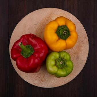 Draufsicht farbige paprika auf schneidebrett auf hölzernem hintergrund
