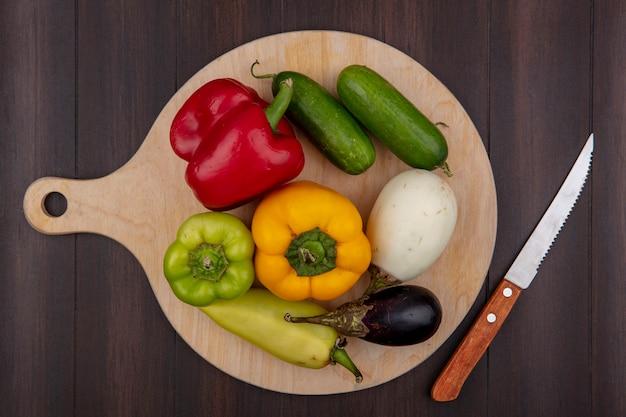 Draufsicht farbige paprika mit bklazana und gurke auf einem schneidebrett mit einem messer auf einem hölzernen hintergrund