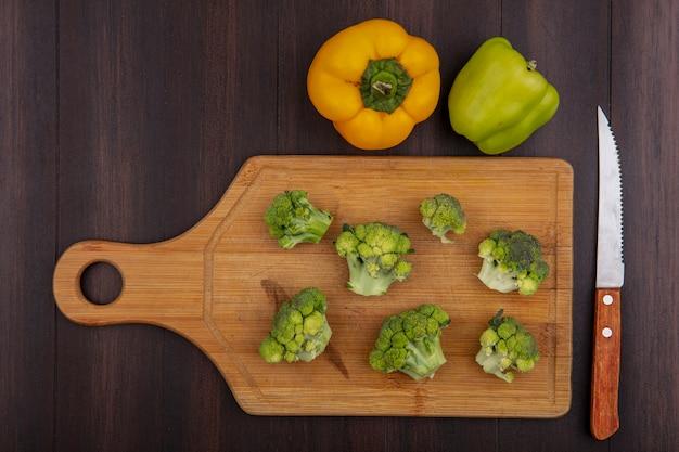 Draufsicht farbige paprika mit brokkoli auf schneidebrett mit messer auf holzhintergrund
