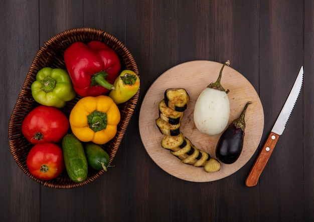 Draufsicht farbige paprika mit gurken und tomaten in einem korb mit auberginen auf einem schneidebrett mit einem messer auf einem hölzernen hintergrund