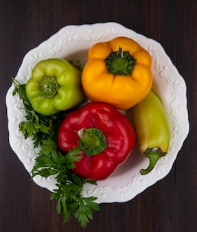 Draufsicht farbige paprika mit petersilie in einer platte auf hölzernem hintergrund