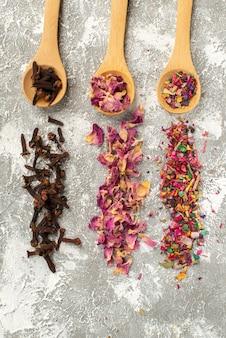 Draufsicht farbiger getrockneter tee auf weißem oberflächenblumenpflanzenbaumgeschmackstaub