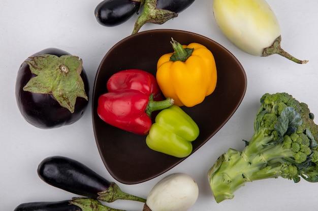 Draufsicht farbiger paprika in einer schüssel mit auberginen und brokkoli auf einem weißen hintergrund