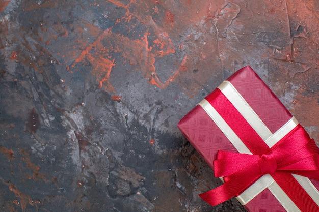 Draufsicht-feiertagsgeschenk in rotem paket mit roter schleife auf brauner oberflächenfarbe dunkelheit liebes-zuneigungs-geschenkpaar