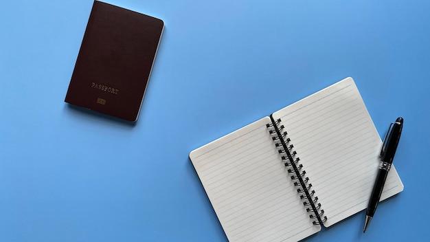Draufsicht flach auf leere seite notizbuch in einer linie mit schwarzem stift und reisepass auf blauem hintergrund